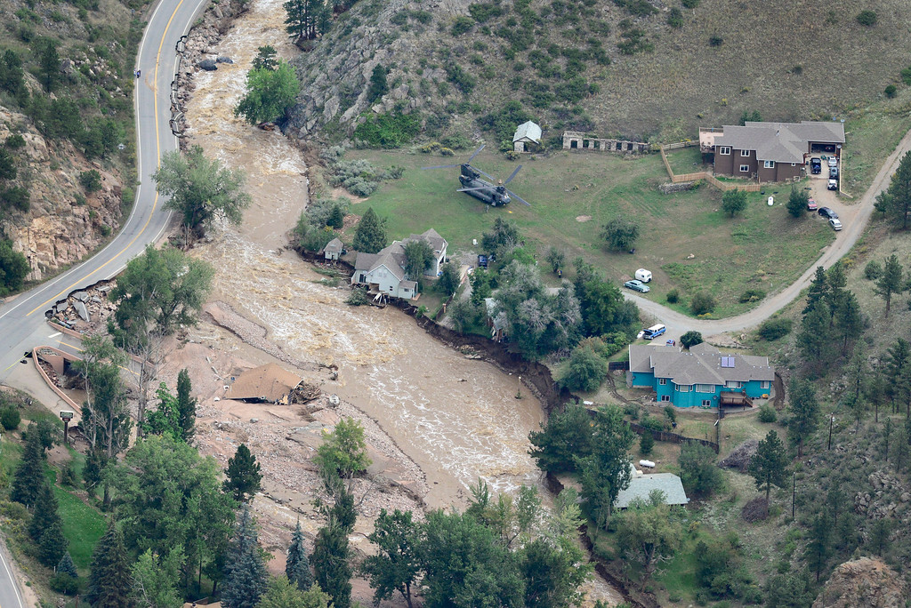 . A Colorado National Guard chinook helicopter is seen helping to evacuate residents near Lyons, Saturday, Sept. 14, 2013. U.S. 36 is seen to the top left of the photo. A washed out Longmont Dam Road and flooding St. Vrain River are seen in the lower left. (Matthew Jonas/Times-Call)