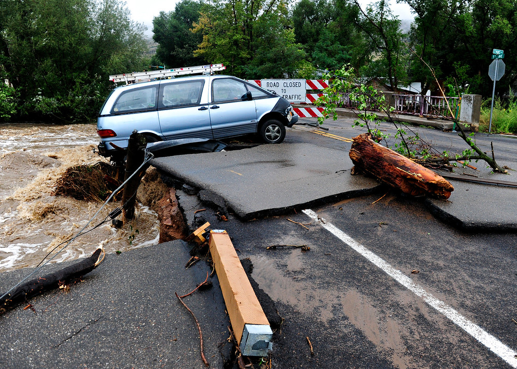 . A van sits precariously along the edge of the bridge at Fifth Avenue in Lyons Friday, Sept. 13, 2013.  (Greg Lindstrom/Times-Call)