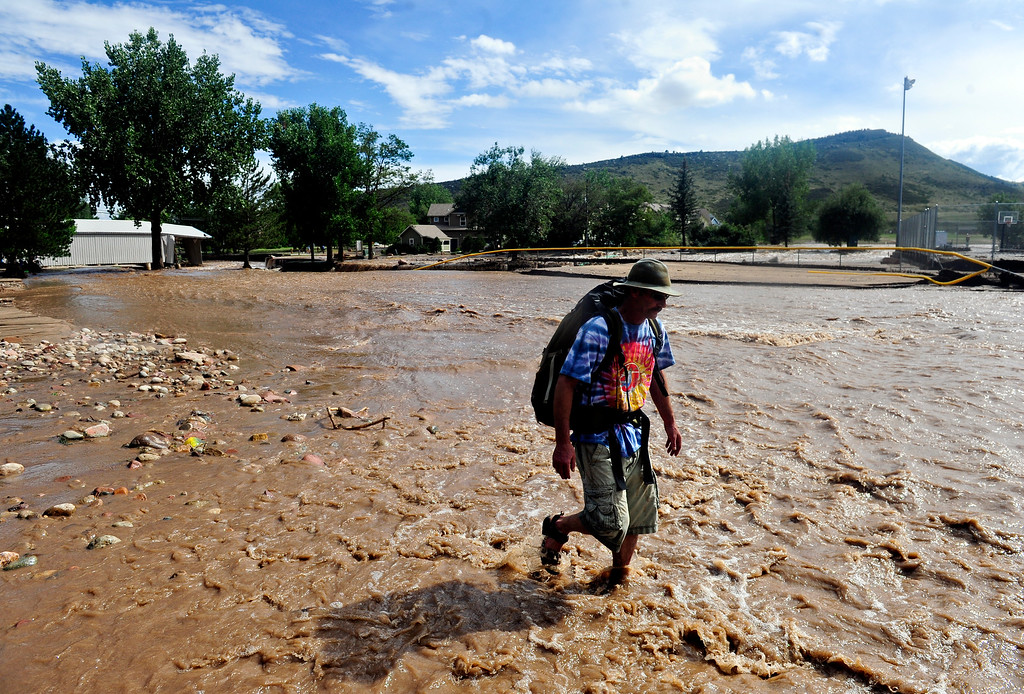 . Chris Melani wades through floodwater near Bohn Park after coming into town for supplies Friday, Sept. 13, 2013. Melani lives up Red Gulch on the southwest side of town, and is isolated from the rest of town. (Greg Lindstrom/Times-Call)