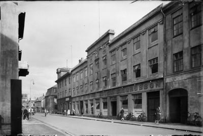 Um 1930   Borgarmynd, götumynd  Hafnarstræti 10-12. Verslunin Edinborg, Ásgeir Sigurðsson. Breska ræðismannsskrifstofan H.Ólafsson & Bernöft, vörubifreið og fólk á reiðhjólum.