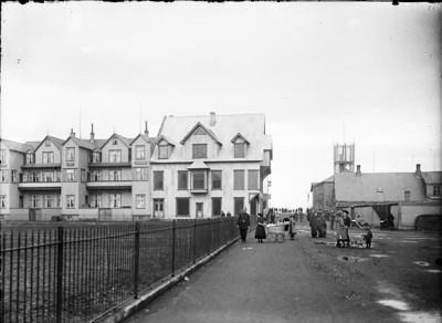 1906-1910   Borgarmynd, götumynd, fólk  Pósthússtræti Austurstræti 12, Hótel Reykjavík Austurstræti 14, Syndikatið Austurstræti 16. Konur og stúlka með barnavagna og lögregluþjónn.