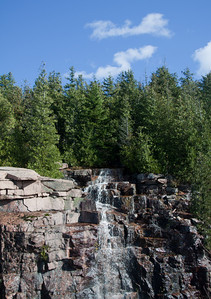 waterfall after rain cascading down granite rock face with blue sky and native cedar trees, Acadia National Park, Mount Desert Island Maine
