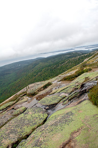 View west from atop Cadillac Mountain (formerly known as Green Mountain) looking across granite knoll with green lichen. Acadia National Park, Mount Desert Island, Maine, September