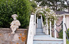 coastal Maine garden scenic, blue stairs, garden statuary of little boy on stone wall covered with orange lichen, pink climbing rose, New Dawn on white arbor. This would be a pretty place to photograph a bride. Westpoint Village, Phippsburg Maine, summer, July 2012