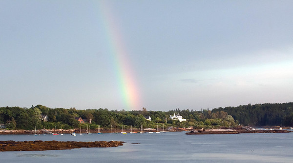 rainbow on Small Point, Phippsburg Maine, falling at where the historic, former Block House sat, near Alliquippa, also known as Ancient Augusta, summer. The field of moored sailboats is the Small Point Sailing club