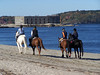Horseback riding on Popham Beach, Phippsburg Maine with Fort Popham in the background. Looking north up the Kennebec River