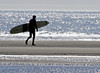 Surfer carrying board on Popham Beach State Park in glittering sun. Phippsburg, Maine summer