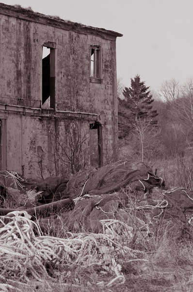abandoned sardine processing factory in Eastport, Maine, black and white, nets and lines of discarded fishing gear in foreground