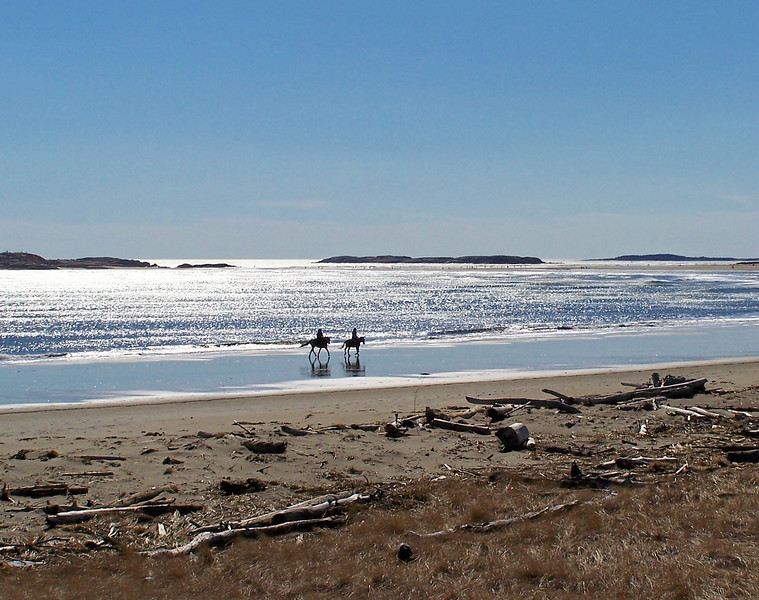 Horseback riding at Popham Beach State Park, Phippsburg, Maine. The ledges in the middle background are The Three SIsters, sometimes called The Herons, Maine scenic