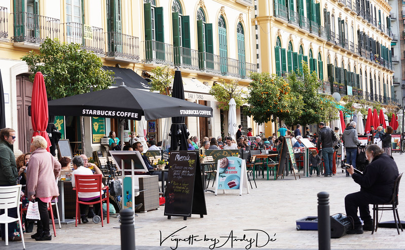 Candid camera capture of a street side cafe in Malaga with a minstrel playing his violin.