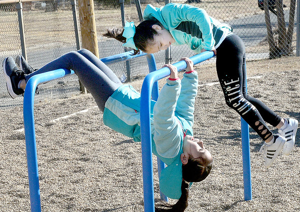 Kevin Harvison | Staff photo<br /> Kimberly Llamas and Brianna Nava enjoy hanging out on the excersise bars during an Emerson Elementary School recess.