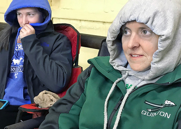 KEVIN HARVISON | Staff photo<br /> Pictured from left, Rynda Wilson and Relinda Wilson of Quinton, attempt to stay warm inside the livestock barn before the start of the Pittsburg County Livestock Show begins Thursday.