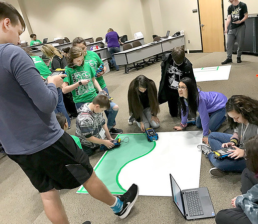 KEVIN HARVISON | Staff photo A group of students work on coding before taking the rover out to the challenge portion of the competition Wednesday at the Lucy Smith building in McAlester.