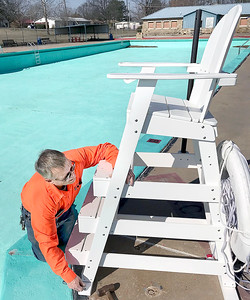 KEVIN HARVISON | Staff photo Clifford Vanderpool, Certified Pool Operator for City of McAlester, starts the pool prep as he anchors down a life guard chair at Jeff Lee Pool.