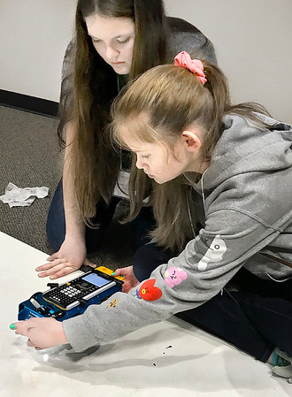 KEVIN HARVISON | Staff photo Puterbaugh students pictured from left, Annabelle Carrell and her partner Sierra Cain work on coding before taking the rover out to the challenge portion of the competition Wednesday at the Lucy Smith building in McAlester.