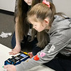 KEVIN HARVISON | Staff photo<br /> Puterbaugh students pictured from left, Annabelle Carrell and her partner Sierra Cain work on coding before taking the rover out to the challenge portion of the competition Wednesday at the Lucy Smith building in McAlester.
