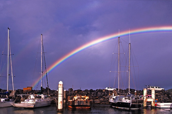 Rainbow over waterfront maritime marina/dock with boats.