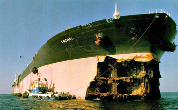 1994 - 06/01 - June 1st - TOCHAL  - IMO7386910 - Tanker - 151225GRT/300068DWT - 347.6 x 53.7 - 1977 Astilleros Astano, El Ferrol, No.242 as MUNDACA - 1984 OCEAN CLOUD, 1984 YUCATAN VALLEY, 1985 UMM AL MADAFA, 1986 TOCHAL - Iranian National Tanker Co. -  bound from the Gulf to Europe with 270,000 tonnes of crude, became a casualty off the Cape of Good Hope when her bow structure failed in heavy weather. With the tanker in danger of becoming a total loss a salvage agreement had to be promptly concluded with Pentow Marine whose powerful tug WOLRAAD WOLTEMADE was already on standby. With the vessel at the time some 70 nautical miles west of Dassen Island, a three-man diving team from South African Diving Services (SADS) was flown out to undertake preliminary damage assessment. In the open sea and with a heavy swell running, the divers videotaped the massive damage where the entire 30m x 22m bulbous bow section had sheared off. Having obtained permission for the vessel to take shelter in False Bay, the TOCHAL was towed stem first whilst the dive tender vessel REUNION, with a full diving spread and a 12-man team, was made ready to meet the vessel on its arrival. In the meanwhile, using portable pumps taken out to the TOCHAL, the diving team assisted in pumping oil from the forward fuel tank into empty cargo tanks. As oil was pumped out so the tank filled with sea-water from cracks in the bottom tank plating, caused when the bow fell away. On arriving in False Bay a comprehensive underwater video survey was undertaken whilst preparations were made to transfer the oil cargo to the lighter tanker, OSLO PRINCESS, which was on standby in the bay. With the collision bulkhead acting as a breakwater, diving conditions were very difficult and dangerous as the team worked around the clock for almost four days to trim and cut away damaged plates, most of which were recovered for insurance purposes. With the ship-to-ship transfer of oil underway, the divers were able to commence patc