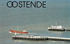 BELGIUM - OSTENDE - A nice little Danish coaster sails from Ostende between the long curving breakwaters.