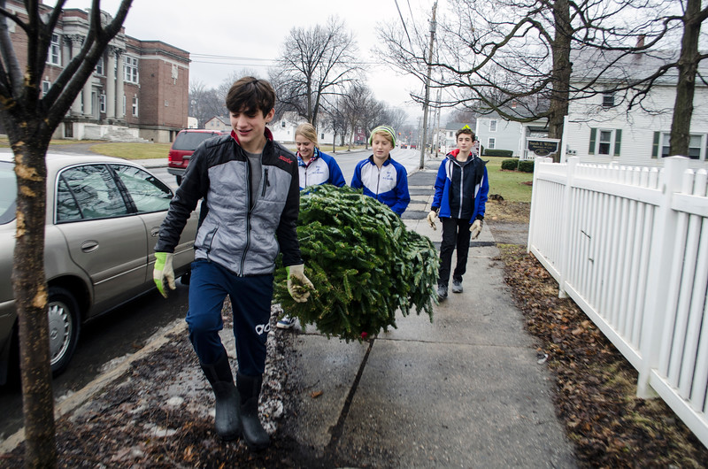 David LaChance — Bennington Banner<br /> Members of the MAU Nordic Ski Team, from left, Chase Dobson, Sarah Umphlett, Sam Umphlett and Leo Herbert, carry away a Christmas tree on Main Street in Bennington during the team's annual tree collection Saturday. More than 200 trees were disposed of during the team's largest annual fundraiser, which aimed to raise $2,000 for equipment and wax.