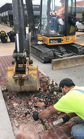 Kevin Harvison | Staff photo<br /> McAlester city employees work to remove damaged bricks in the new sidewalk at the intersection of First Street and Choctaw Avenue. City workers believe the damage was due to foundation problems from the original street.