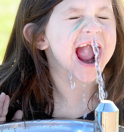 Kevin Harvison | Staff photo<br /> Rayanna Duncan is surprised by the water pressure at the Chadick Park water fountain as she misses her mouth and gets a blast of water up her nose.