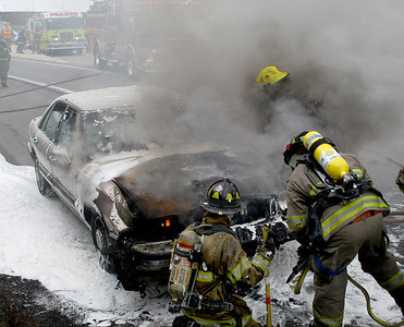 PICTURE BY FRANK ANDRUSCAVAGE  Mahanoy City firefighters work to extinguish a car on fire on Route 54 in Mahanoy Township Friday afternoon.