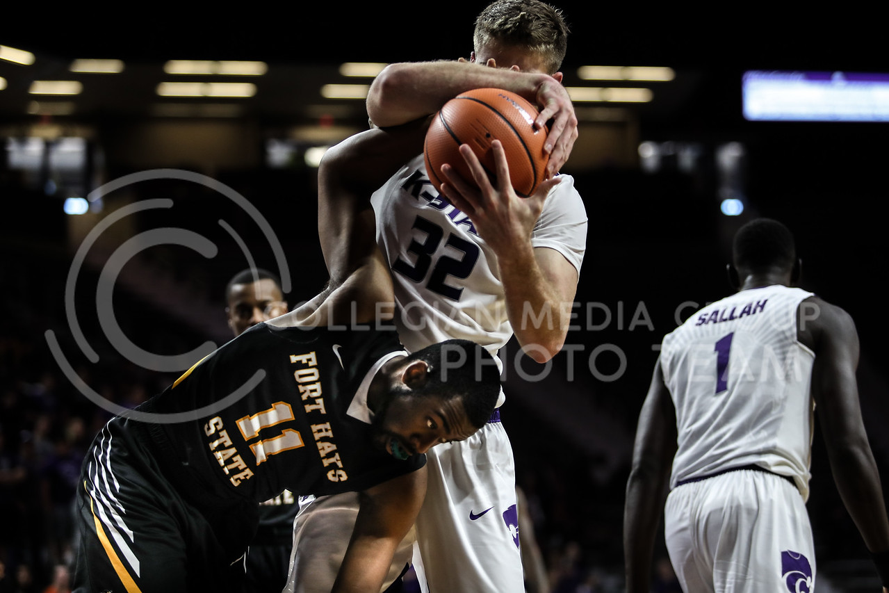 MANHATTAN, KANSAS - OCTOBER 29: Kansas State #32 Dean Wade wrestles the ball out of Fort Hays #11 Marcus Cooper's hands during the men's basketball game between Fort Hays State University and Kansas State University at Bramlage Coliseum on October 29, 2017. (Photo by Cooper Kinley | K-State Athletics)