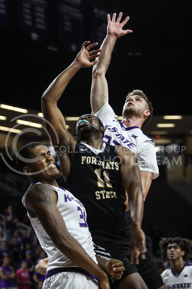 MANHATTAN, KANSAS - OCTOBER 29: #32 Dean Wade reaches for a rebound during the men's basketball game between Fort Hays State University and Kansas State University at Bramlage Coliseum on October 29, 2017. (Photo by Cooper Kinley | K-State Athletics)