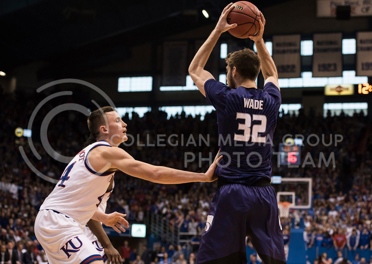 Kansas State Wildcat number 32, Dean Wade, prepares to pass the ball over Kansas Jayhawk number 44, Mitch Lightfoot, during the Sunflower Showdown at Allen Fieldhouse in Lawrence, Kan., on Jan. 13, 2018. (Olivia Bergmeier | Collegian Media Group)