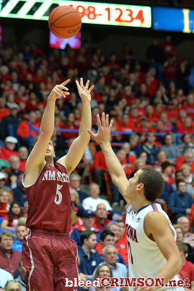 December 11, 2013: New Mexico State Aggies guard Kevin Aronis (5) shoots over Arizona Wildcats forward Brandon Ashley (21) in a game between No. 1 Arizona and New Mexico State at McKale Center in Tucson, Ariz. Arizona defeated New Mexico State 74-48.