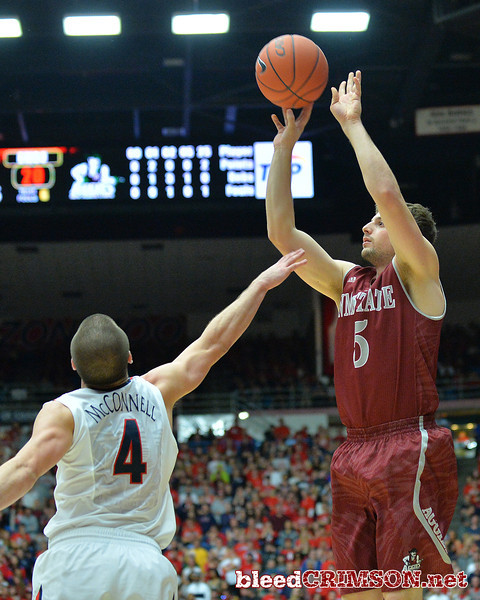 December 11, 2013: New Mexico State Aggies guard Kevin Aronis (5) shoots over Arizona Wildcats guard T.J. McConnell (4) in the first half in a game between No. 1 Arizona and New Mexico State at McKale Center in Tucson, Ariz. Arizona defeated New Mexico State 74-48.