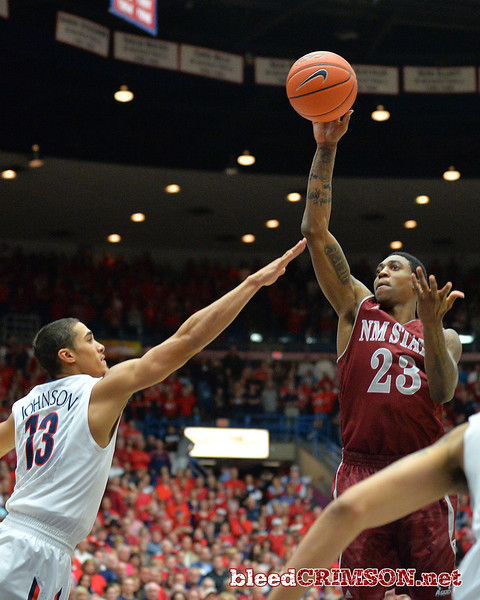 December 11, 2013: New Mexico State Aggies guard Daniel Mullings (23) puts up a floater over Arizona Wildcats guard Nick Johnson (13) in the first half  in a game between No. 1 Arizona and New Mexico State at McKale Center in Tucson, Ariz. Arizona defeated New Mexico State 74-48.