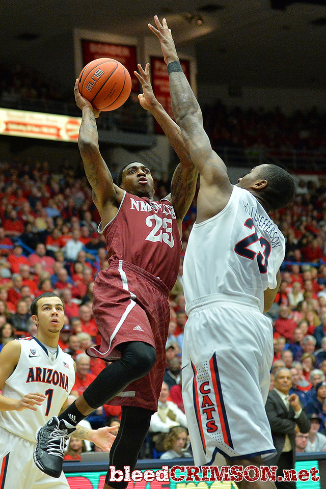 December 11, 2013: New Mexico State Aggies guard Daniel Mullings (23) puts up a shot over Arizona Wildcats forward Rondae Hollis-Jefferson (23) in a game between No. 1 Arizona and New Mexico State at McKale Center in Tucson, Ariz. Arizona defeated New Mexico State 74-48.