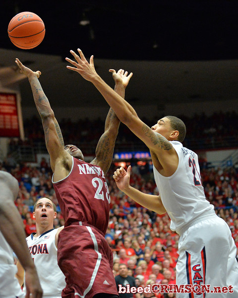 December 11, 2013: New Mexico State Aggies guard Daniel Mullings (23) and Arizona Wildcats forward Brandon Ashley (21) battle for a rebound in a game between No. 1 Arizona and New Mexico State at McKale Center in Tucson, Ariz. Arizona defeated New Mexico State 74-48.