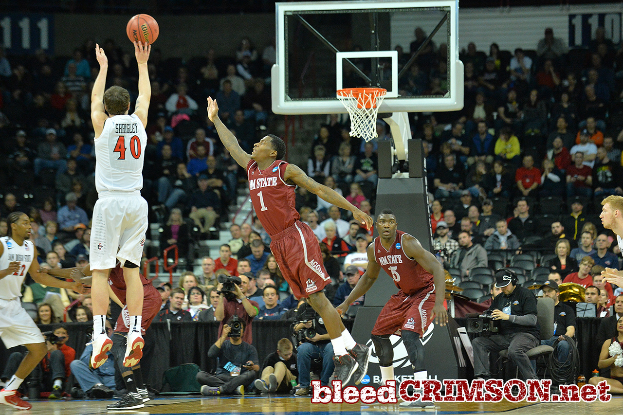March 20, 2014: New Mexico State Aggies guard DK Eldridge (1) tries to contest a three point shot by San Diego State Aztecs forward Matt Shrigley (40) during a second round game of the NCAA Division I Men's Basketball Championship between the 4-seed San Diego State Aztecs and the 13-seed New Mexico State Aggies at Spokane Arena in Spokane, Wash. San Diego State defeated New Mexico State 73-69 in overtime.