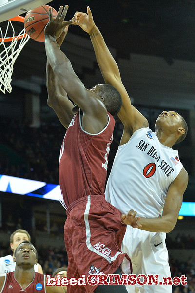 March 20, 2014: New Mexico State Aggies has his shot contested by San Diego State Aztecs forward Skylar Spencer (0) during a second round game of the NCAA Division I Men's Basketball Championship between the 4-seed San Diego State Aztecs and the 13-seed New Mexico State Aggies at Spokane Arena in Spokane, Wash. San Diego State defeated New Mexico State 73-69 in overtime.
