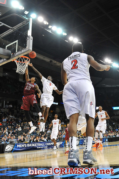 March 20, 2014: New Mexico State Aggies guard Daniel Mullings (23) has his layup attempt blocked by San Diego State Aztecs forward Dwayne Polee II (5) during a second round game of the NCAA Division I Men's Basketball Championship between the 4-seed San Diego State Aztecs and the 13-seed New Mexico State Aggies at Spokane Arena in Spokane, Wash. San Diego State defeated New Mexico State 73-69 in overtime.