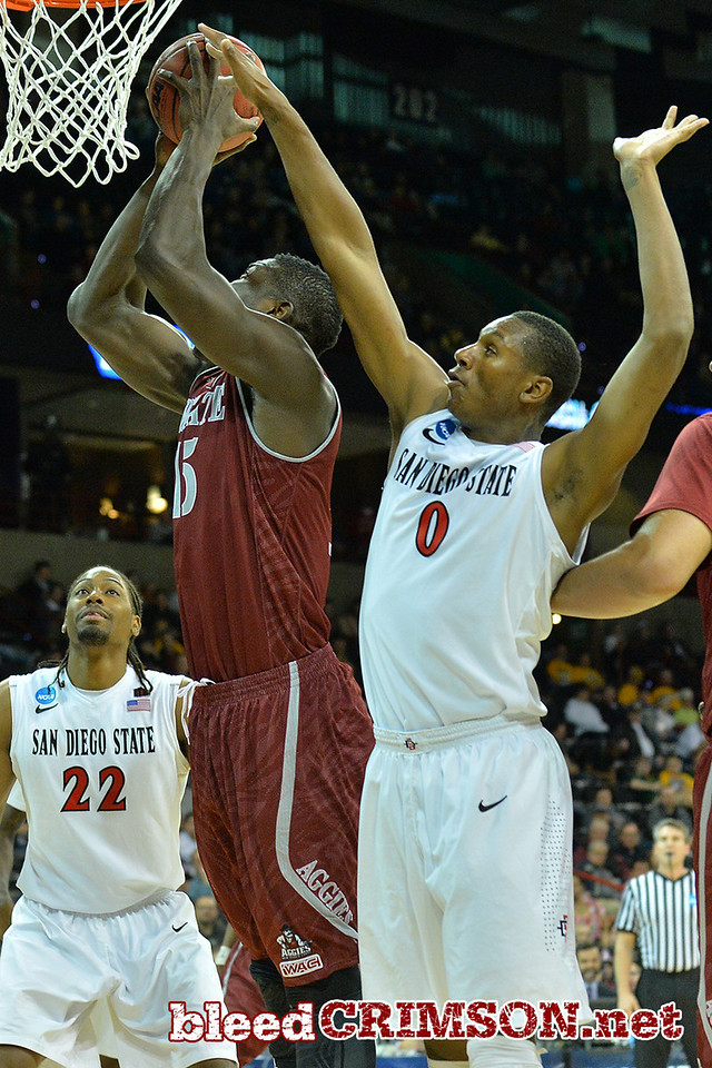 March 20, 2014: New Mexico State Aggies center Tshilidzi Nephawe (15) has his shot blocked by San Diego State Aztecs forward Skylar Spencer (0) during a second round game of the NCAA Division I Men's Basketball Championship between the 4-seed San Diego State Aztecs and the 13-seed New Mexico State Aggies at Spokane Arena in Spokane, Wash. San Diego State defeated New Mexico State 73-69 in overtime.
