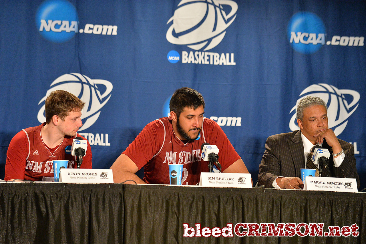 March 20, 2014: New Mexico State Aggies head coach Marvin Menzies, New Mexico State Aggies center Sim Bhullar (2) and New Mexico State Aggies guard Kevin Aronis (5) talk to the media in the post game press conference after a second round game of the NCAA Division I Men's Basketball Championship between the 4-seed San Diego State Aztecs and the 13-seed New Mexico State Aggies at Spokane Arena in Spokane, Wash. San Diego State defeated New Mexico State 73-69 in overtime.