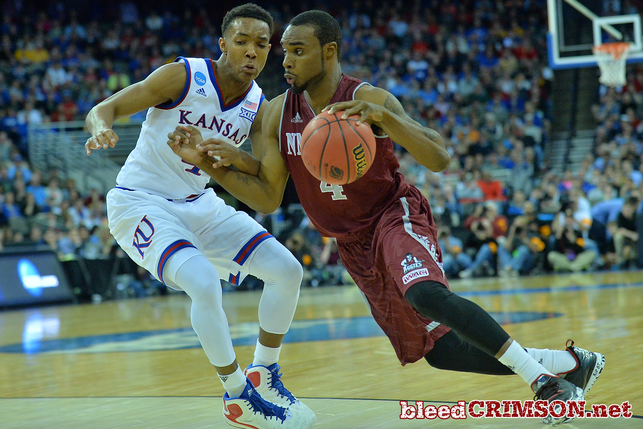 March 20, 2015: New Mexico State Aggies guard Ian Baker (4) drives past Kansas Jayhawks guard Devonte Graham (4) during a second round game between No. 15 New Mexico State and No. 15 Kansas in the 2015 NCAA Men's Basketball Championship Tournament at CenturyLink Center in Omaha, Neb.
