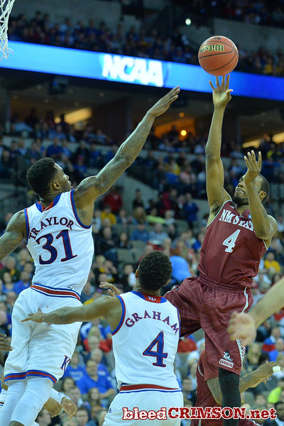 March 20, 2015: New Mexico State Aggies guard Ian Baker (4) puts up a shot over Kansas Jayhawks forward Jamari Traylor (31) during a second round game between No. 15 New Mexico State and No. 15 Kansas in the 2015 NCAA Men's Basketball Championship Tournament at CenturyLink Center in Omaha, Neb.