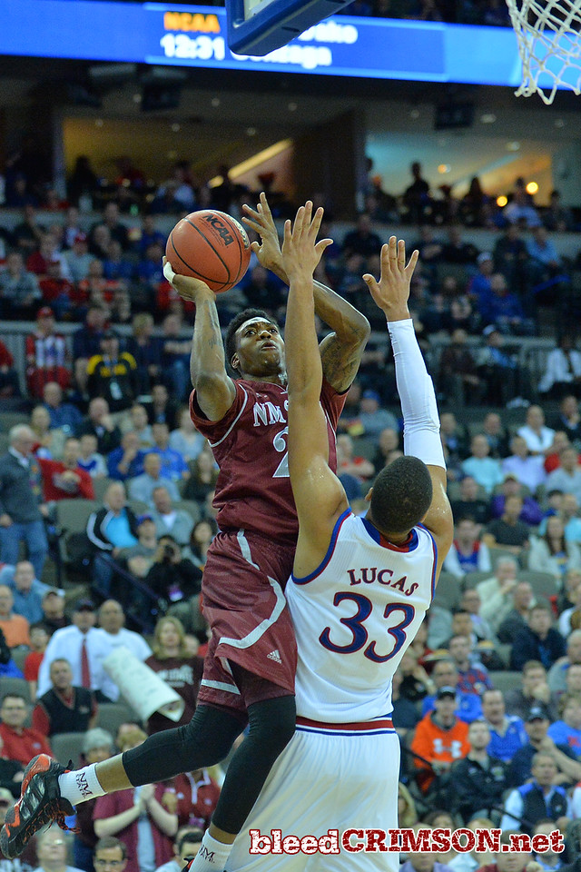 March 20, 2015: New Mexico State Aggies guard Daniel Mullings (23) puts up a shot over Kansas Jayhawks guard Wayne Selden Jr. (1) during a second round game between No. 15 New Mexico State and No. 15 Kansas in the 2015 NCAA Men's Basketball Championship Tournament at CenturyLink Center in Omaha, Neb.