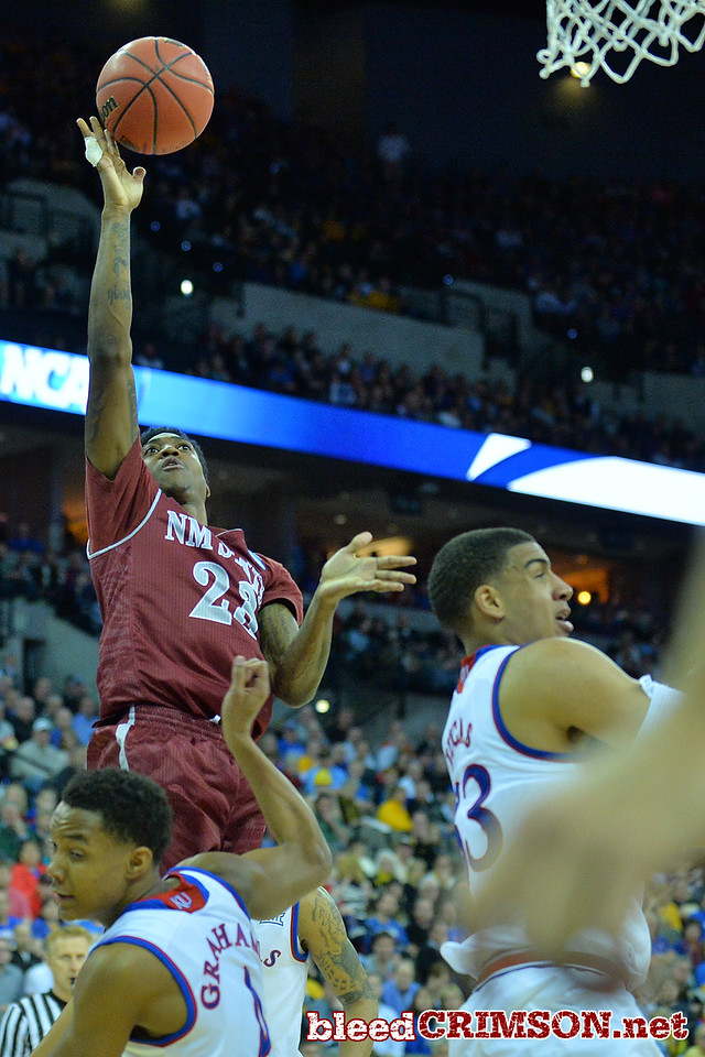 March 20, 2015: New Mexico State Aggies guard Daniel Mullings (23) puts up a shot over Kansas Jayhawks guard Devonte Graham (4) during a second round game between No. 15 New Mexico State and No. 2 Kansas in the 2015 NCAA Men's Basketball Championship Tournament at CenturyLink Center in Omaha, Neb.