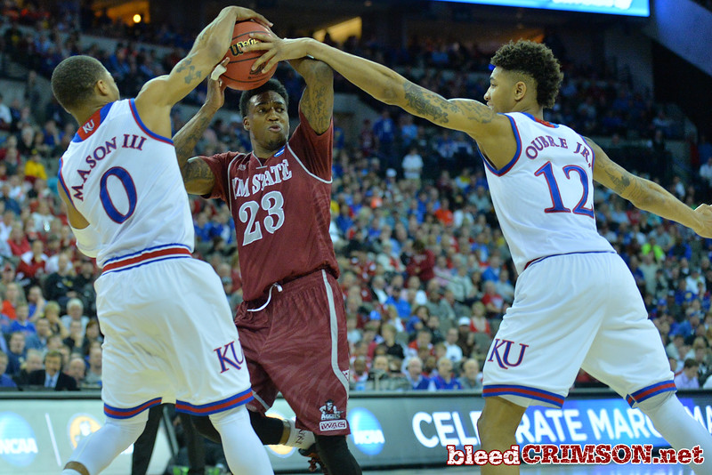 March 20, 2015: New Mexico State Aggies guard Daniel Mullings (23) is guarded by Kansas Jayhawks guard Frank Mason III (0) and Kansas Jayhawks guard Kelly Oubre Jr. (12) during a second round game between No. 15 New Mexico State and No. 15 Kansas in the 2015 NCAA Men's Basketball Championship Tournament at CenturyLink Center in Omaha, Neb.