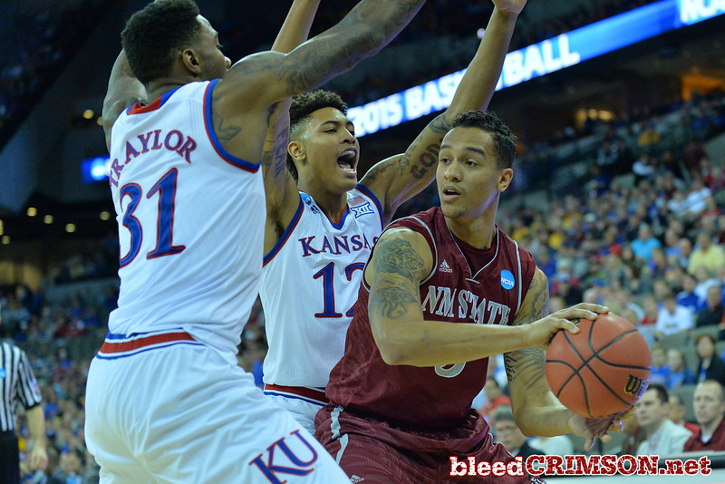 March 20, 2015: New Mexico State Aggies forward Remi Barry (3) looks to pass the ball through the defense of Kansas Jayhawks forward Jamari Traylor (31) and Kansas Jayhawks guard Kelly Oubre Jr. (12) during a second round game between No. 15 New Mexico State and No. 2 Kansas  in the 2015 NCAA Men's Basketball Championship Tournament at CenturyLink Center in Omaha, Neb.