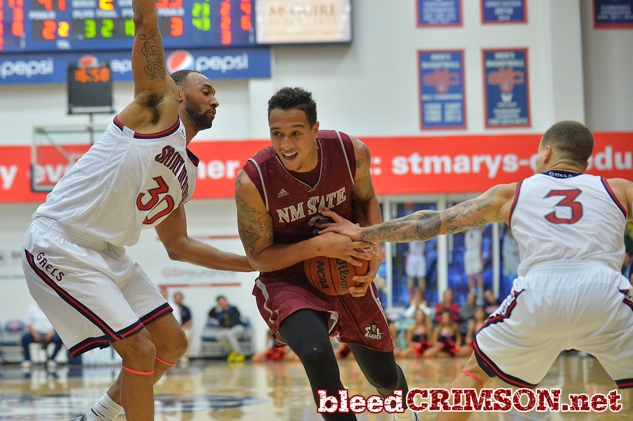 Nov. 18, 2014: New Mexico State Aggies forward Remi Barry (3) drives to the basket between St. Mary's Gaels forward Desmond Simmons (30) and St. Mary's Gaels guard Kerry Carter (3) during a game between New Mexico State vs. St. Mary's College in Moraga, Calif. in the ESPN College Hoops Tipoff Marathon. Saint Mary's defeated New Mexico State 83-71.