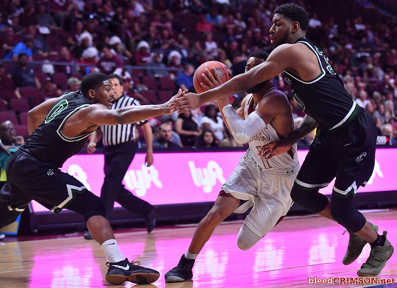 LAS VEGAS, NV - MARCH 08:  Shunn Buchanan #1 of the New Mexico State Aggies drives against Glen Burns #0 and Montana Byrd #32 of the Chicago State Cougars during a quarterfinal game of the Western Athletic Conference basketball tournament at the Orleans Arena in Las Vegas, Nevada. The Aggies won 97-70.