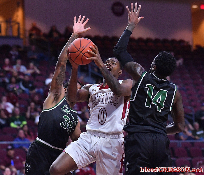 LAS VEGAS, NV - MARCH 08:  Keyon Jones #0 of the New Mexico State Aggies drives against Travon Bell #30 and Fred Sims Jr. #14 of the Chicago State Cougars during a quarterfinal game of the Western Athletic Conference basketball tournament at the Orleans Arena in Las Vegas, Nevada. The Aggies won 97-70.