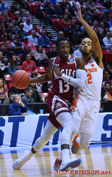 SAN DIEGO, CA - MARCH 16:  Sidy N'Dir #13 of the New Mexico State Aggies drives against Marcquise Reed #2 of the Clemson Tigers during a first round game of the Men's NCAA Basketball Tournament at Viejas Arena in San Diego, California.  (Photo by Sam Wasson)